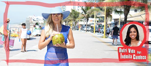 mulher tomando água de coco na praia