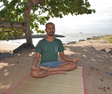 homem meditando na praia macaé