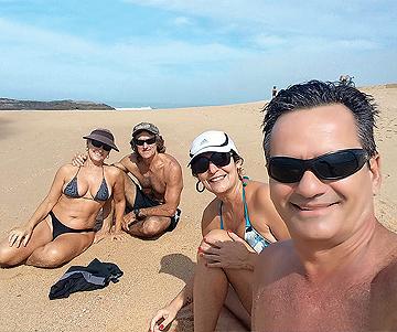 pessoas na praia sentadas na areia